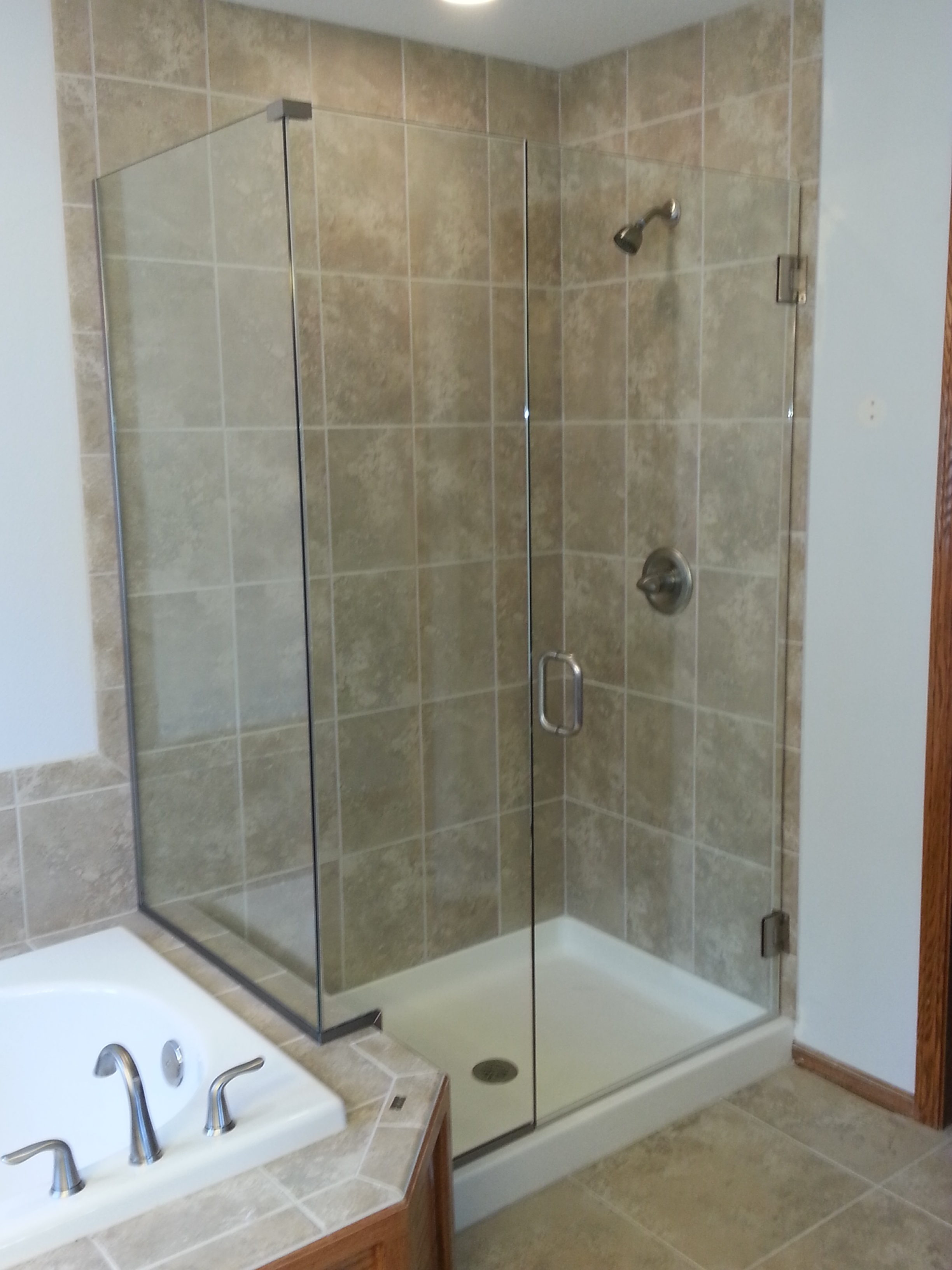 Frameless door and notched inline panel, with a return panel. The panels are installed using channel. Clear glass with brushed nickel hardware, and a C-Pull handle.