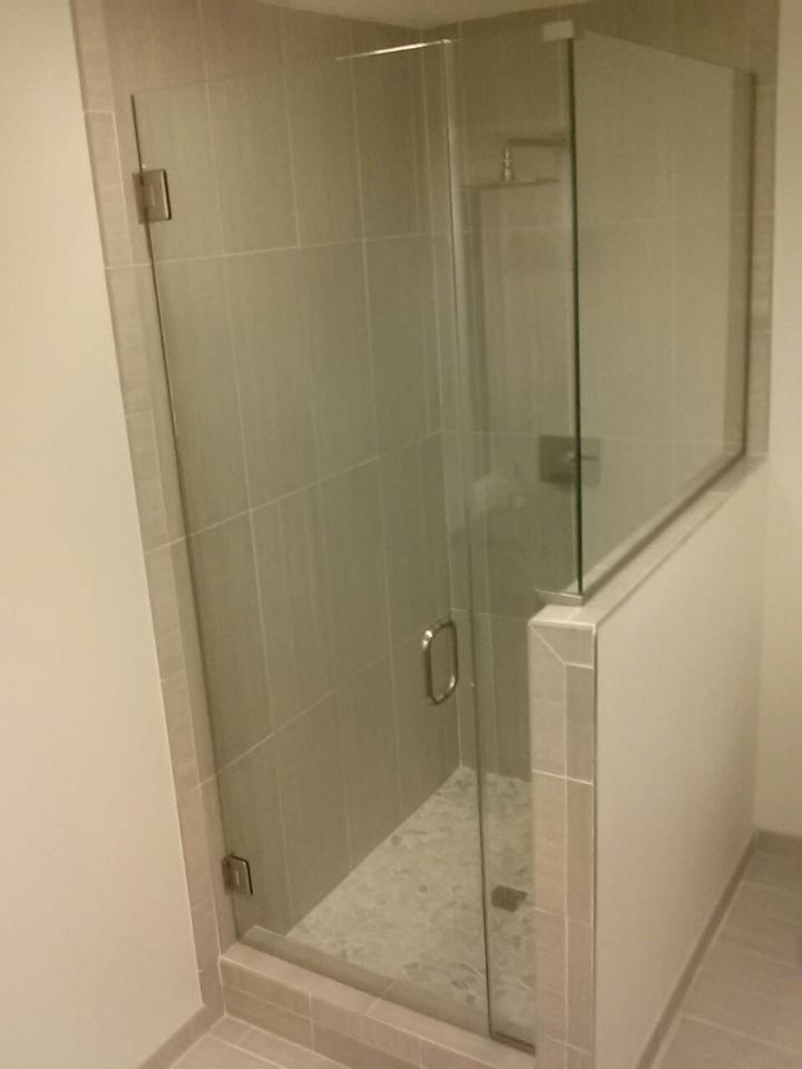 Small frameless enclosure with a notched panel and a return panel on a knee wall. The panel is installed using channel.