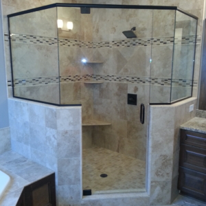 Large neo angle frameless pivot shower doorCorner shower with 4 panels on a knee wall and a header. The panels are installed using channel. Clear glass and oil rubbed bronze hardware with the door using pivot hinges.