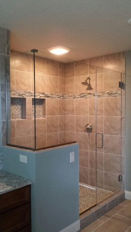 Frameless shower enclosure with a large notched panel and small return on a knee wall. The panels are installed using channel. This enclosure has brushed nickel channel and clear glass.