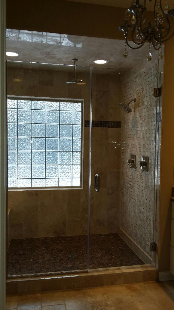 Frameless door and inline panel, installed with chrome channel and hardware.