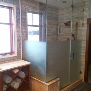 Large frameless enclosure with the bottom of the glass sandblasted for privacy. This enclosure has a door with a transom above, plus an inline notched panel and a return panel resting on a knee wall. The panels are installed using brushed nickel channel and the door has a Coda style handle.