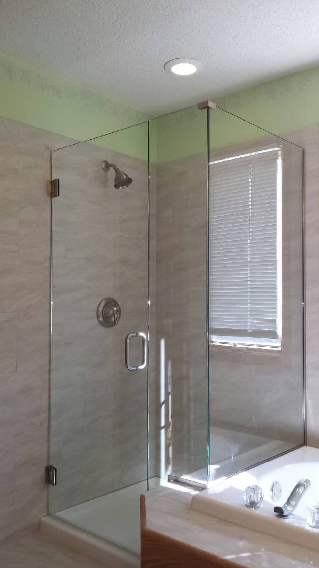 Frameless enclosure with a notched panel and a return panel on a knee wall. The panels are installed with channel. This door has clear glass and brushed nickel hardware.