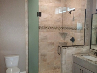 Large frameless enclosure with one floor to ceiling panel frosted for privacy, and another small panel on a knee wall. This enclosure has clear and satin etch glass, and oil rubbed bronze hardware. The panels are installed using channel.