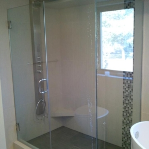 Frameless shower door with inline and return panel using over sleeve clamps, c-pull handle, and offset hinges using chrome u-channel