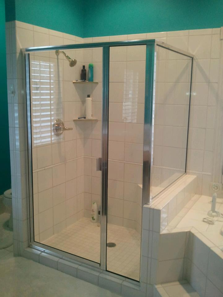Chrome hardware clear glass shower door with panel and notched return on butress