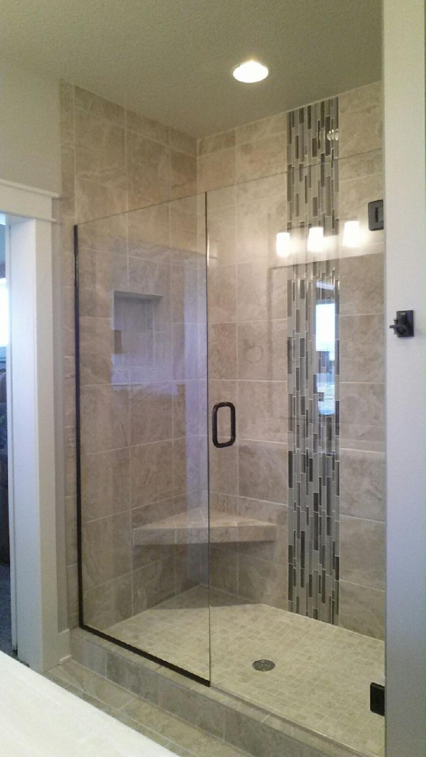 Clear Frameless door and inline panel. The panel is installed using oil rubbed bronze channel.